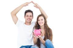 Молодые пары сидя на поле с копилкой Стоковое Изображение