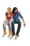 Молодые пары сидя на пустом знамени Стоковое фото RF