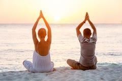 Молодые пары сидя на пляже моря в positi лотоса Стоковые Фото