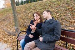 Молодые пары сидя на скамейке в парке в осени Стоковые Изображения RF
