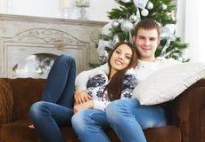 Молодые пары сидя на софе рождественской елкой Стоковое Изображение
