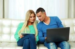 Молодые пары сидя на софе Стоковая Фотография