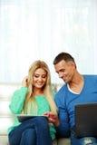 Молодые пары сидя на софе Стоковые Фото