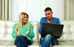 Молодые пары сидя на софе Стоковое фото RF