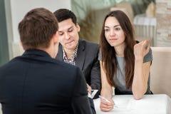 Молодые пары сидя на таблице и разрешают их проблемы с a Стоковые Изображения
