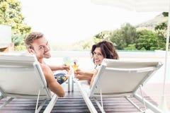 Молодые пары сидя на loungers солнца Стоковые Фото
