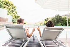 Молодые пары сидя на loungers солнца Стоковые Фотографии RF