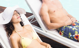 Молодые пары сидя на loungers солнца Стоковые Изображения