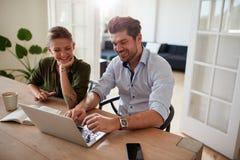 Молодые пары сидя совместно и работая на компьтер-книжке Стоковое Изображение