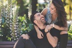 Молодые пары сидя совместно смеяться над снаружи Стоковое фото RF