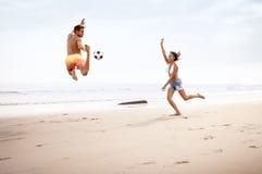 Молодые пары смешанной гонки играя с футболом Стоковое Изображение RF