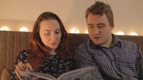 Молодые пары смотря кассету или книгу дома сток-видео