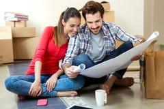 Молодые пары смотря светокопии их нового дома стоковые изображения