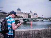 Молодые пары советуют с умным телефоном на мосте над Сеной в p Стоковое фото RF
