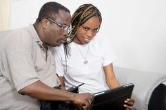 Молодые пары совместно используя компьтер-книжку стоковая фотография