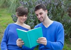 Молодые пары совместно читая книгу совместно в парке Стоковые Фотографии RF