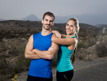 Молодые пары спорта представляя совместно холодную и усмехаясь счастливую склонность девушки на плече человека Стоковое Изображение