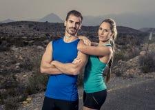Молодые пары спорта представляя совместно холодную и усмехаясь счастливую склонность девушки на плече человека Стоковая Фотография