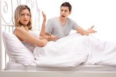 Молодые пары споря в кровати стоковое изображение rf