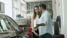 Молодые пары споря и выбирают автомобиль в автосалоне сток-видео