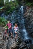Молодые пары стоя близко водопад с их велосипедами стоковое фото