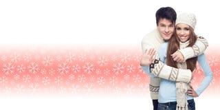 Молодые пары стоя над предпосылкой зимы Стоковое Изображение