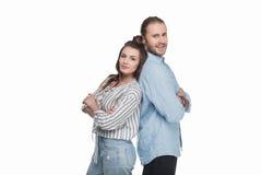 Молодые пары стоя спина к спине и усмехаясь на камере Стоковое Изображение RF