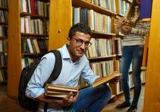 Молодые пары студента выбирая книги в библиотеке стоковое изображение rf