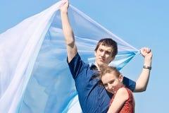 Молодые пары с белым шарфом против голубого неба Стоковое фото RF
