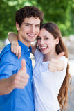 Молодые пары с большими пальцами руки вверх стоковое фото rf