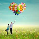 Молодые пары с воздушными шарами Стоковые Изображения RF