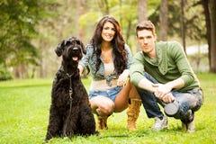 Молодые пары с гигантским шнауцером Стоковая Фотография