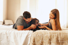 Молодые пары с их собакой на кровати в утре Стоковое Изображение