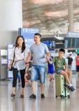 Молодые пары с мальчиком на чемодане на международном аэропорте столицы Пекина Стоковое фото RF