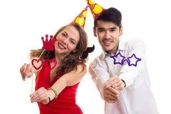 Молодые пары с ручками карточки и шляпами праздновать Стоковая Фотография