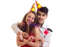 Молодые пары с ручками карточки и шляпами праздновать Стоковое Изображение