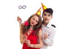 Молодые пары с ручками карточки и шляпами праздновать Стоковое Изображение RF