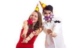 Молодые пары с ручками карточки и шляпами праздновать Стоковые Изображения RF