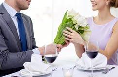 Молодые пары с стеклами вина на ресторане Стоковое фото RF