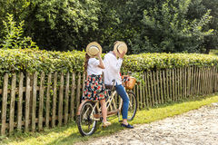 Молодые пары с тандемом велосипеда в парке Молодые люди держит их шляпы в их руках, закрывая их стороны Стоковая Фотография