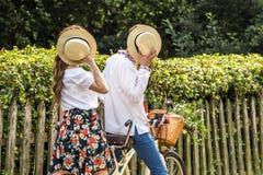 Молодые пары с тандемом велосипеда в парке Молодые люди держит их шляпы в их руках, закрывая их стороны Стоковое Фото