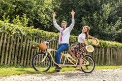 Молодые пары с тандемом велосипеда в парке Молодые люди держит шляпы в их руках и улыбке На задней части загородки дерева Стоковое Изображение
