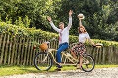Молодые пары с тандемом велосипеда в парке Молодые люди держит шляпы в их руках и улыбке На задней части загородки дерева Стоковые Изображения