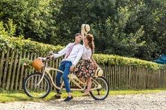 Молодые пары с тандемом велосипеда в парке Молодые люди держит шляпы в их руках и улыбке На задней части загородки дерева Стоковое Фото
