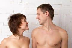 Молодые пары с шаловливыми эмоциями около белой стены Стоковые Фото