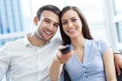 Молодые пары с remote ТВ Стоковое фото RF