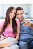 Молодые пары с remote TV Стоковое Изображение