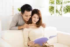 Молодые пары тратя время читая совместно на софе Стоковое фото RF