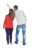 Молодые пары указывая на wal задний взгляд (женщина и человек) Стоковые Фото
