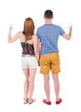 Молодые пары указывая на wal задний взгляд Стоковая Фотография